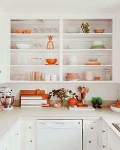 Beautiful white kitchen with pops of orange and green. It's almost like a modern version of a 50s kitchen.