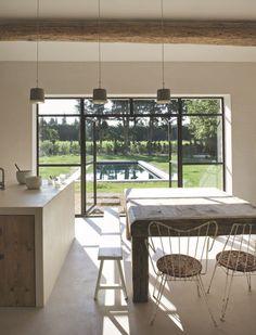 La cuisine associe un îlot central et un plan en béton blanc à des éléments en pin de récupération créés sur mesure par Laurent Passe-LP Design.