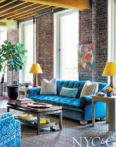 A custom tufted sofa covered in #Schumacher blue velvet | Tilton Fenwick Puts a Fresh Spin on a Traditional Artist's Loft in SoHo | New York Cottages & Gardens