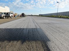 Asphalt paving fabric, tack coat and prepared asphalt surface (foreground, after grinding) in an asphalt paving operation at a warehouse complex in West Sacramento, Calif.