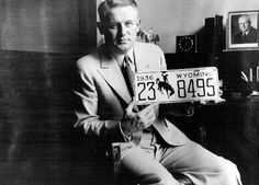 Secretary of State (later Governor) Lester Hunt holding the 1936 Wyoming license plate, the first to feature the bucking horse logo. Hunt commissioned Colorado artist Allen True to design the logo. Whether True intended the cowboy and horse to represent anyone in particular is up for debate. Photo from the Wyoming State Archives.
