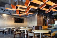 Interior decor is contemporary, young and energetic. Inspired by the logo of the restaurant, perforated dots create dancing shapes on the bronze backdrop. Grey colour mirror film laminated glasses divide the booth seats and the custom made pinwheel pendent lamps give the warm orange shade to the restaurant.