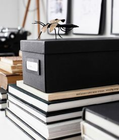 Home office storage stacked on books- black, white and neutral colour palette.