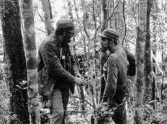 キューバのシエラ・マエストラの森の中で、キューバ革命の指導者、エルネスト・チェ・ゲバラ氏(右)と話す、もう一人の指導者、フィデル・カストロ氏(1957年10月8日撮影)。(c)AFP
