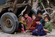 Afghan refugee girls sit behind a wooden cart in a slum on the outskirts of Islamabad; Muhammed Muheisen/Associated Press