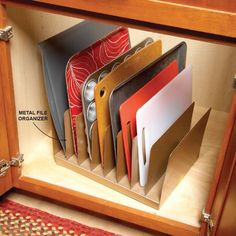 Instant Kitchen Cabinet Organizer - A metal file organizer is perfect for storing baking sheets, cutting boards and pan lids. You can pick one up for a buck at a dollar store. To keep the organizer from sliding around, use rubber shelf liner or attach hook-and-loop tape to the cabinet base and the bottom of the organizer.