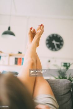 Stock-Foto : Legs of woman lying on couch at home