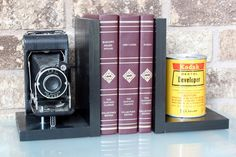 Original Kodak Junior Six-20 Camera, and an original Kodak Film development chemical can – modified into a pair of bookends. The camera and can are in excellent condition with some signs of years of service.  These are original photography artifacts (camera, and can) and not reproductions. The bookends are also a great gift and add a little vintage feel to any room. They are picture-perfect for the photography fan or the vintage lover.  Each Bookend is 5 1/2 (width) x 6 (deep) x 8 1&#x2F...