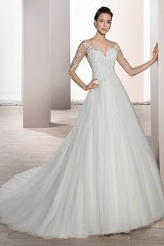 Classic meets contemporary with this romantic Ball gown featuring Venice lace over barely there illusion sleeves and lace bodice that transitions into a low dramatic sheer back with covered buttons. The tulle skirt flows into a Chapel length train. Style 676 by @demetriosbride.