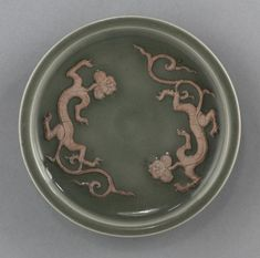 Yuan Dynasty. Dish with two dragons in relief. Glazed porcelain with unglazed molded decoration. 16.5 cm diameter. The Cleveland Museum of Art.