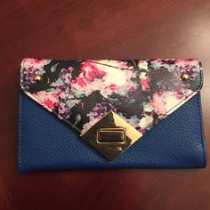 On sale todayfloral print clutch/wallet NWT's floral print clutch style wallet. 12 slot card holder and 1 slot for ID. 1 large zipper slot 3 spacious slots for cash, receipts & check book. Clasp front closure. Bags Clutches & Wristlets