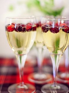 Adding frozen cranberries to your champagne gives your signature cocktail a fall twist. Photo by Jodi Miller Photography via The Brides Cafe.
