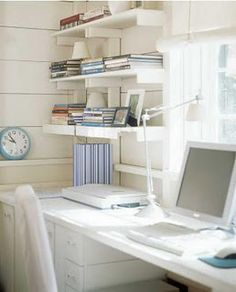 Desk along window with wall shelves