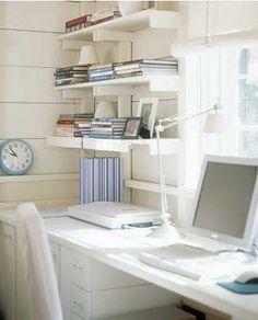 Desk along window with wall shelves
