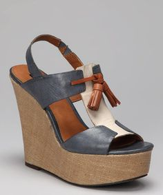 A classic T-strap silhouette with a comfy elastic slingback crafted out of rich burnished leather sits atop a chunky fabric-covered wedge for a wow-worthy look packed with polished style.