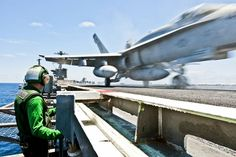 U.S. Navy Airman Matthew Fulks observes flight operations as an F/A-18C Hornet launches off the flight deck of the aircraft carrier USS John C. Stennis under way in the Pacific Ocean, July 6, 2012. The John C. Stennis is conducting sustainment exercises off the coast of California designed to maintain mission readiness. U.S. Navy photo by Seaman Nolan Kahn