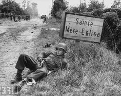 US soldier Elmer Habbs of Delaware resting next to sign post as troops advance on the 2nd day of the Allied invasion of Normandy. France, 7 June 1944.