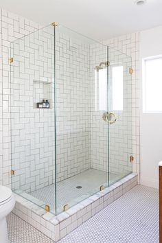 Amazing master bathroom boasts seamless glass shower accented with brass hardware fitted with subway tiles laid out in geometric pattern and Kohler Purist Shower Head in Brushed Gold as well as Merola White Hex Tiles on shower floor.