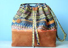 Bolsa Saquinho em tecido 100% algodão dublado , <br>com estampa folk. <br>Fundo em camurça caramelo. <br> <br>Bolso frontal com zíper. <br>Forrada e com bolso interno. <br>Alça regulável <br> <br>Medidas: <br>altura: 32 cm <br>largura: 26 cm <br>profundidade: 15 cm