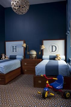 Fantastic boys' bedroom with David Trubridge - Coral 400 Pendant Lamp, blue walls paint color, twin wood monogram beds, brown & Blue David Hicks Colony Rug and blue bedding.