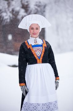 The bunad has a short wool jacket with fine silk ribbon edging. The white festive apron is decorated with crochet lace.