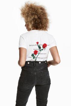 Weiß/Rosen. T-Shirt aus weichem Baumwolljersey. Modell mit Motivdruck und fixiertem Ärmelumschlag.