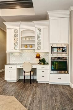 Desk area and display hutch in Kitchen with built-in wall oven and microwave. Cross grid cabinetry with lantern tile backsplash. Mannington hardwood flooring in grey and black.