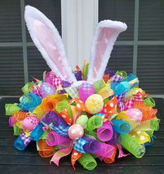 20 diameter Mesh and Ribbon centerpiece with Bunny Ears and Easter Eggs. Style of decorative items, such as bunny ears and eggs, are subject to availability and may not be exactly as picture shown.  ***The bunny ears shown in this pic are no longer available. Future orders for this item will contain a different style of ears. Still adorable though