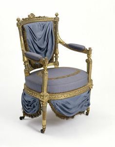 Armchair made of carved walnut, painted white and grey and partly gilt with reproduction silk upholstery and modern castors created by Jean-Baptiste-Claude Sené [Paris, France], c. 1790. At the top of this chair is carved the monogram MA for Marie-Antoinette, Queen of France. It is unknown which of her palaces it comes from, although Sené supplied similar suites of chairs to her at the Château de Saint-Cloud, at Versailles and at the Tuileries