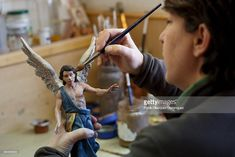Mercedes Munoz paints an Angel clay figurine at Jose Luis Mayo's workshop on December 16, 2014 in Madrid, Spain. Jose Luis Mayo is a recognized artisan and the only in Madrid that produces hand made original clay figurines for Christmas Nativity Scenes. Jose Luis learned to work with clay on his own and keeps studying the culture and society of that epoch. At his workshop he has a team that reproduces handmade copies of his works on clay or ceramic.