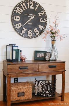 plank wall, large clock and spring flowers in the entryway