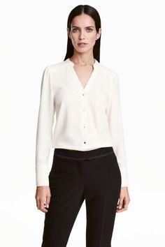 Camisa com mangas tufadas: Camisa com decote em V em crepe ligeiramente grosso. Tem pequena gola subida, botões de pressão a toda a altura da frente, mangas compridas tufadas e punhos altos com botões de pressão.