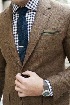 Brown suit, gingham shirt, blue necktie and tie bar.