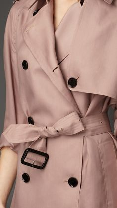Burberry directional trench coat is crafted in a refined showerproof silk with an organza-like texture. Heritage details, including the gun flap, epaulettes and rain shield, are worked in oversize dimensions for a modern feel. The relaxed-fit trench coat is structured with raglan sleeves and a belted waist