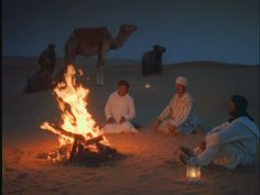 Middle Eastern men in turbans sitting by campfire in desert at night / camels in background / Morocco