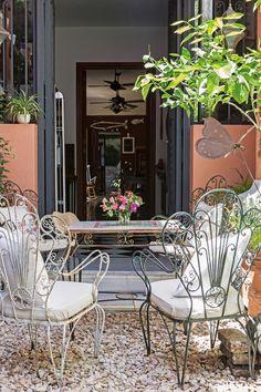 Patio en clave romántica con juego de jardín de hierro, integrado a una gran cocina comedor rústica.