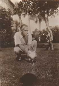 American playwright and Nobel Laureate, Eugene O'Neill squatting on lawn, holding pet rooster, named Marcia. (1934).