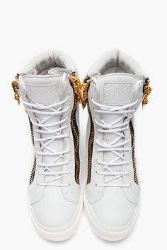 GIUSEPPE ZANOTTI //  White Pebbled Leather Sharktooth High-Top Sneakers  32266M050007  High-top pebbled leather sneakers in white. Round toe. Gold tone hardware. White lace up closure. Tonal leather logo patch at tongue. Signature zip closures at eyerow with sharktooth-shaped metal zipper pulls. Paneled upper. Padded collar. Off-white rubber foxing. Tonal stitching. Leather upper, rubber sole. Made in Italy.  $975 CAD