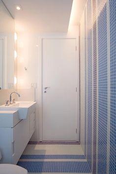 Banheiro com pastilha azul dando um pouco de cor ao ambiente. Os detalhes da iluminação fazem toda a diferença.