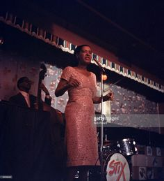 American jazz singer Billie Holiday (1915-1959) performs on stage accompanied by a drummer and an upright bass player at the Sugar Hill nightclub, Newark, New Jersey.