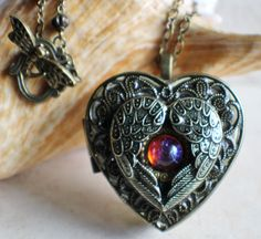 Angel wing music box locket, heart locket with music box inside with dragons breath cabochon.