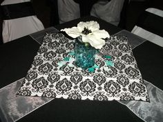 wedding table decor--diy...tablecloth, 2 organza sashes criss-crossed, a hanky in damask print table square, a mason jar and fake amaryllis with black floral embellishments.