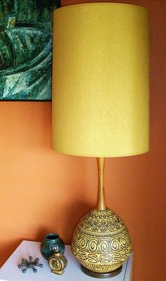 Orange wall. Dark blue contrasting art. ESP loc the skinny tall mid century lamp and shade.