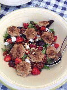 Salade: geroosterd brood met geitenkaas en honing, aardbeien, rucola en pijnboompitten. Dressing: balsamicocreme.