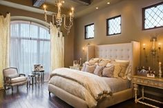 traditional master bedroom with sitting area large window tall tufted head board