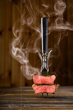 Sliced beef steak on a fork on the wooden table by Kamil Zabłocki on 500px
