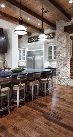 This kitchen looks like it belongs in a ski lodge, with stone accents, high wooden beams and wooden stools. But this rustic charmer is actually in the suburbs, providing a cozy eating spot for the whole family. It also helps that this eat-in-style kitchen is huge! High ceilings, industrial-style lights and dark granite countertops complete the look. via KitchenDailyCanada