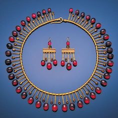 A fine mid 19th century archaeological revival gold, garnet and enamel demi-parure, by Robert Phillips, circa 1865 The necklace designed as a fringe of oval garnet cabochons alternating with smaller batons decorated with black enamel, suspended from a woven gold chain, the bangle with central band enamelled with continuous oval motifs in blue and white enamel and gold bead and wirework decoration, between courses of oval cabochon garnet spokes, the pair of pendent earrings en suite