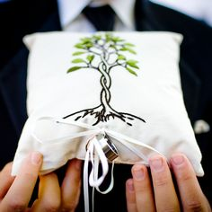 photo of groom holding the ring bearer's pillow with the tree of life design and the wedding rings attached - photo by New Mexico based wedding photographers Twin Lens