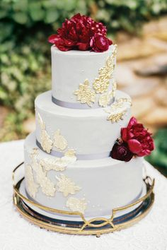 A tiered cake with gold-leaf and floral accents by Cakes by Chloe.